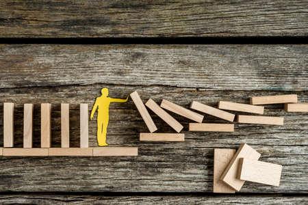 Enige mens die dalende houten bakstenen in een conceptueel beeld van een document knipselsilhouet op een rustieke achtergrond steunt.
