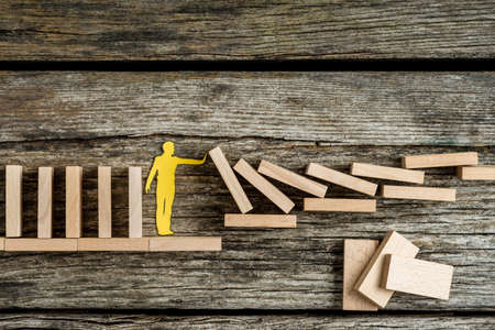 Pojedynczy mężczyzna trzyma spadające drewniane cegły w koncepcyjny obraz sylwetki wyłącznik papieru na rustykalnym tle.