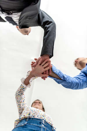 Three business colleagues stacking hands in a gesture of cooperation and teamwork viewed directly from below looking up with focus to their hands.