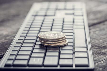 レトロな効果は色あせ、ビットコインサイン付きの金貨の山を持つキーボードの色合いのイメージ。