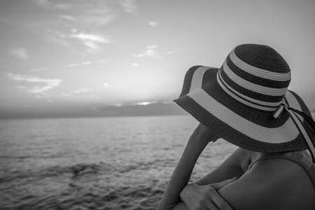 Monochrome image of a woman with stripped straw hat looking into the distance over the ocean under an evening sky.