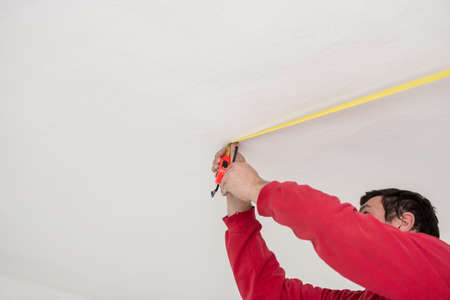 Builder taking a measurement with a tape marking a point on a white interior wall with copy space in a DIY and renovations concept.