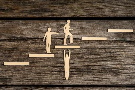 1つのサポートステップを持つ紙の男性を切り取り、1つは後ろから助けを与え、3番目は概念的なイメージで成功へのステップを登ります。