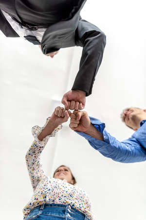 Three business colleagues knocking fists in a motivational gesture of solidarity viewed directly from below looking up with focus to their hands.