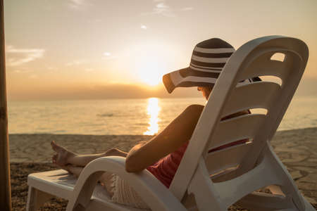 Woman in a large floppy sunhat relaxing on a recliner at the beach at sunset facing out over a tranquil ocean on her summer vacation. 写真素材