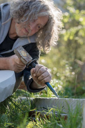 Senior sculptor sculpting with chisel and hammer in stone outdoors.