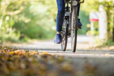 Woman riding a bicycle outdoors on a path in the park in Autumn. Banque d'images
