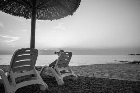 Monochrome image of tropical beach at sunset as a woman relaxes on a deckchair under an umbrella on summer vacation. 스톡 콘텐츠