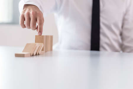 Business man interrupting domino effect by stopping wooden dominoes bricks from crumbling with his finger.