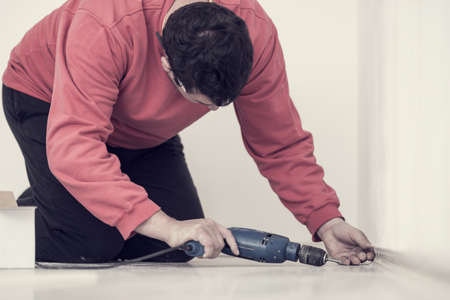 Retro effect faded and toned image of electrician kneeling on the floor drilling a hole in a white interior wall with a handheld electric drill.