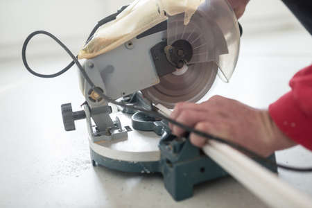 Laborer using a small electric circular saw to cut a length of plastic profile with focus to the power tool.