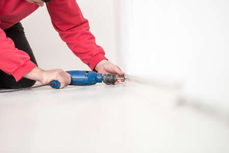 Builder kneeling on the floor drilling a hole in a white interior wall with a small handheld electric drill. Imagens