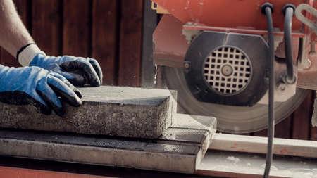 角度グラインダーを使用して、手と電動工具の側面図でコンクリートブロックをカットする作業員、レトロ効果色あせた外観。