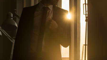 Businessman leaning on a window frame in a shadowy office with a bright sunburst over his shoulder through the window pane.