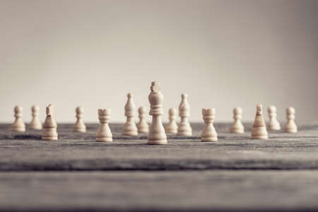Retro image of white chess pieces standing on wooden table in a conceptual image with copy space.