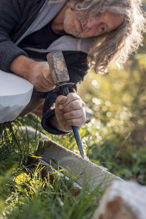 Sculptor sculpting with chisel and hammer in marble stone outdoors. Stock Photo