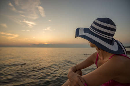 Stylish woman in a trendy straw sunhat relaxing on a beach looking out over the  ocean at sunset, profile view.