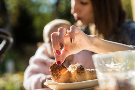 Woman holding a baby as they sit outdoors in the garden in a close up view of her elegant hand with varnished nails taking a piece of croissant off a plate. Stock Photo