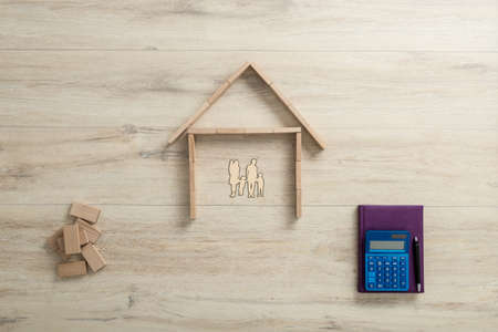 Top view of the shape of a residential house made of building wooden blocks for a family next to a calculator and notebook.
