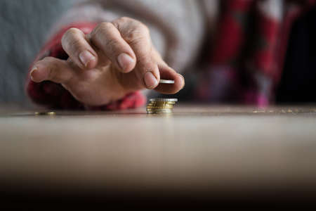 Hand of person with dirty fingers putting coin on pile with table in foreground and copy space.