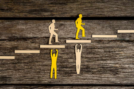 Small silhouette people on top of paper blocks pushing others of opposite color up steps over dark wooden background. Foto de archivo