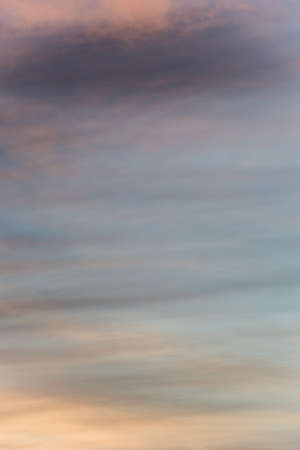 Delicate diffuse sunset sky background with a golden orange glow on a hazy clouds over twilight blue blending to darker clouds at the top.