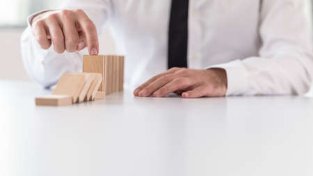 Businessman preventing dominoes from crumbling with finger on white wooden table.