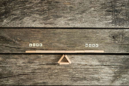 Balancing quality Life time and Work concept with a seesaw of blocks over a rustic wood background with copy space. Фото со стока