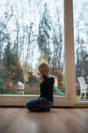 Little blond boy kneeling on a wooden floor at home in front of a glass patio door overlooking the garden with his hand on the glass in evening light.