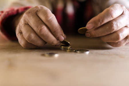Man with dirty hands sitting at his desk counting coins in a conceptual image.