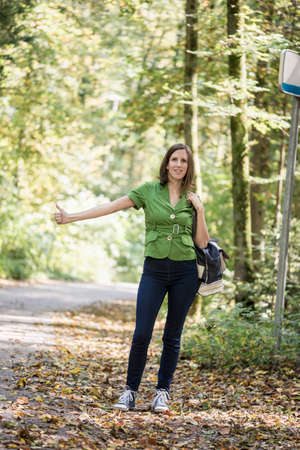 Front view of a woman hitchhiker standing on the side of the road, thumbing for picking her up. Smiling and looking towards camera.