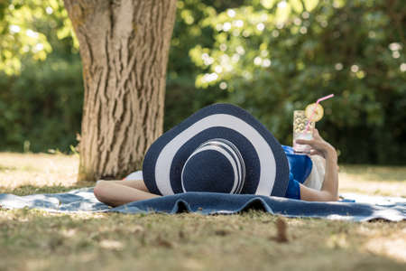 Woman spending a relaxing day in the garden lying in the shade of a tree in her large brimmed sunhat with a cold cocktail in her hand. 스톡 콘텐츠