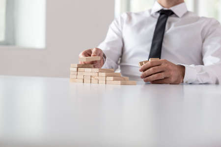 Unidentifiable businessman stacking multiple small wooden blocks on white office table.