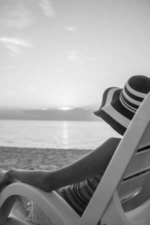 Lonely woman looking at sunset as she relaxes on a recliner chair on the beach on summer vacation in greyscale image.