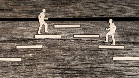Two paper cutout men striving for the same goal or business position climbing steps in opposite directions towards the same platform in a conceptual image of competition. Stock Photo