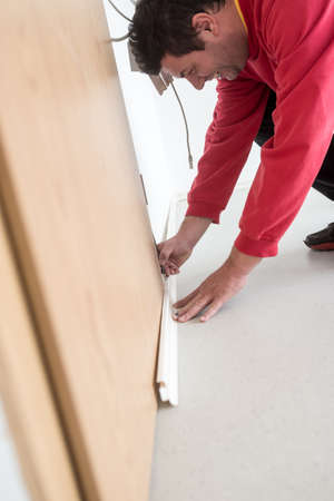 Builder measuring where to cut bending down with a pencil marking off the distance to a wooden door along the angle of the floor and wall in a close up view.
