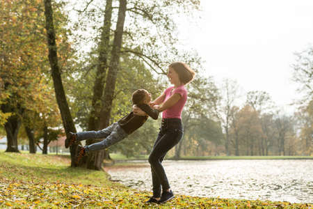 Happy fit young mother playing with her son at the edge of a lake in autumn swinging him around in her arms as she twirls. Stock Photo