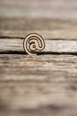 Internet communication concept with a small At icon for a web address standing upright in a crack in rustic wood viewed low angle shallow dof with copy space.