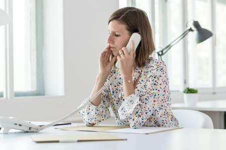 オフィスの机に向かって、横向きに電話をかける真面目な若いビジネスウーマン。 写真素材