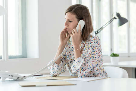 Serious young business woman making a phone call as she sits at her desk in the office, side view.