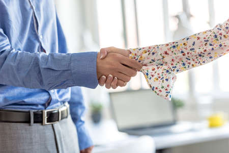 Businessman and woman shaking hands in a close up side view of their arms in a bright airy modern office. Reklamní fotografie