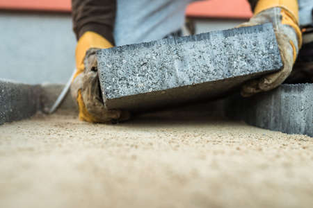 Builder laying a paving brick placing it on the sand foundation with gloved hands. Stock Photo - 98432543