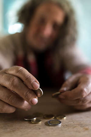 Concept of poor man with dirty hands counting coins at old wooden table. Stock Photo - 98469368