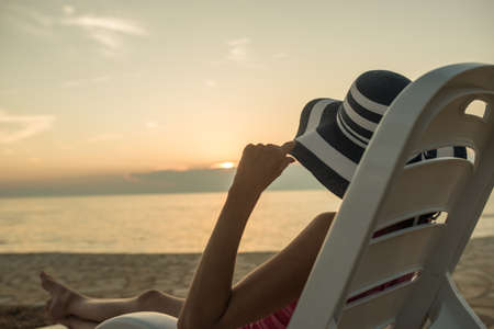 Woman enjoying sunset as she relaxes on a recliner chair on the beach overlooking a calm ocean.