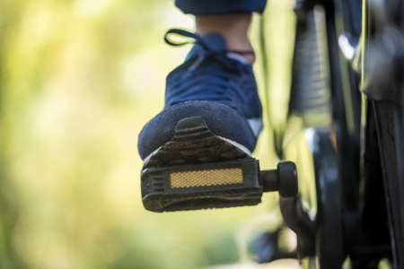 Cropped low angle view of the foot of a person riding a bike outdoors.