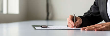 Wide panorama view of businessman hand signing legal or insurance document or business contract on white desk. Stock Photo