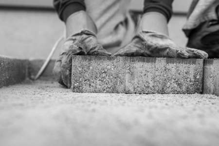 Greyscale image of the gloved hands of a manuel worker laying outdoor paving slabs on a prepared base. Stok Fotoğraf - 99093152