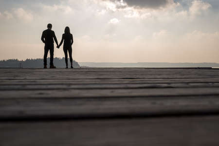Man with woman holding their hands while standing on wooden platform against nature. Stockfoto