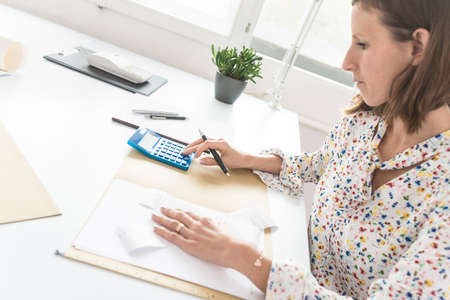 Side high angle view of accountant working at her desk checking figures on blue calculator.