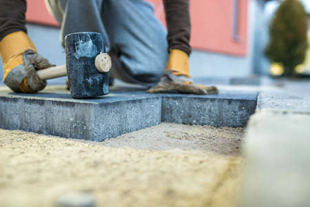 Workman tamping down a new paving brick with a mallet. Stockfoto